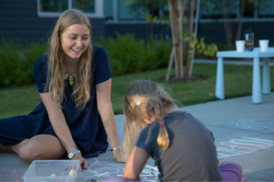 Sanctuary volunteer playing with chalk with young girl