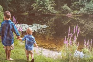 two children walking hand in hand near a pond