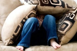 child in cushions on couch