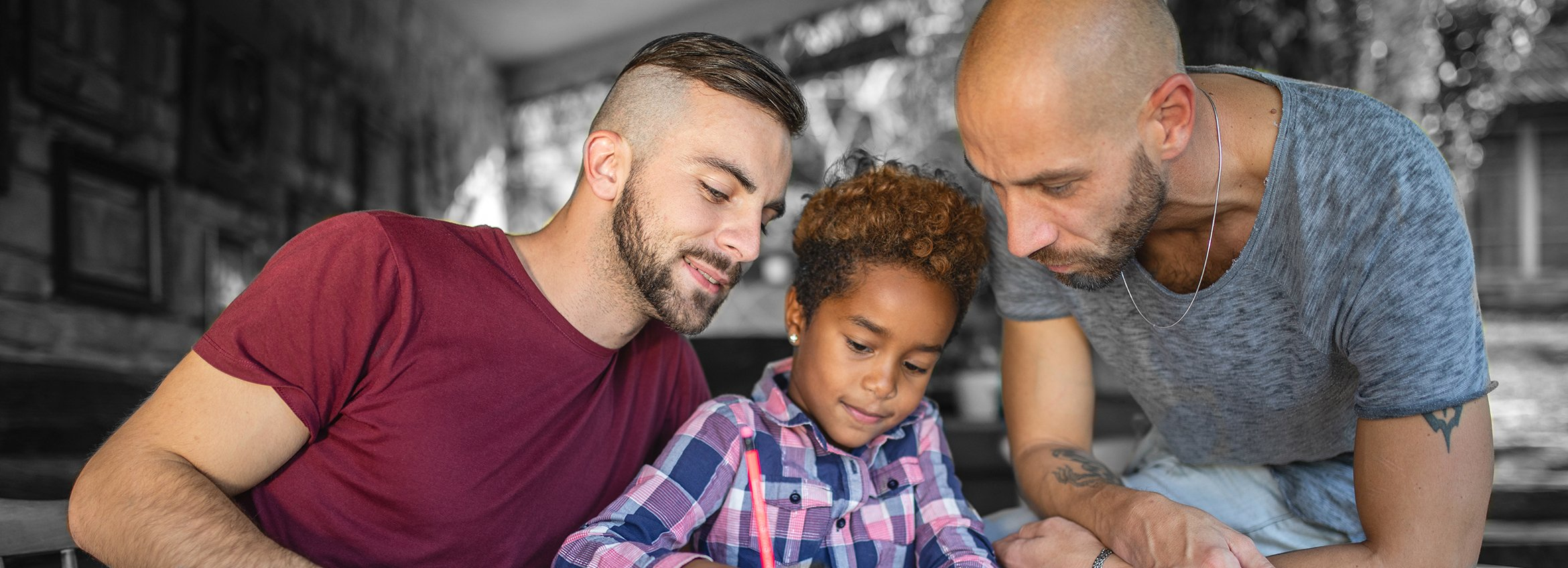Two dads with son helping him write