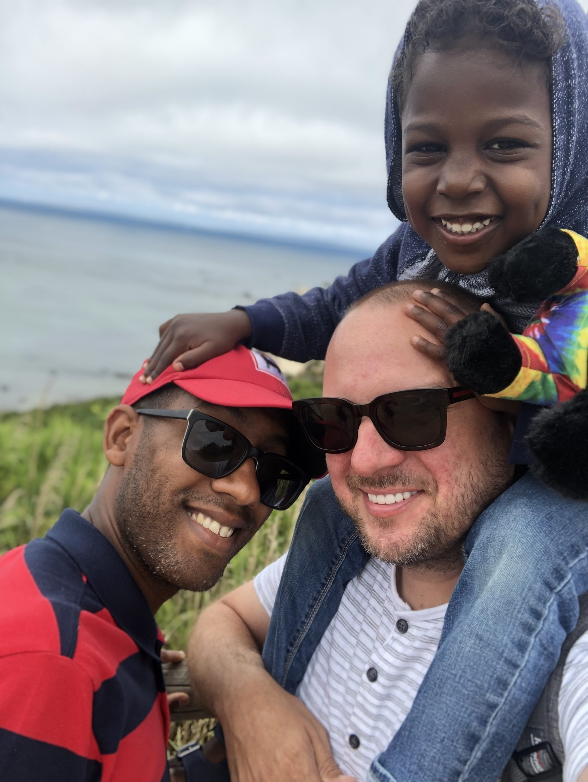 Outdoor photo of Trey with his son on his husband's shoulders