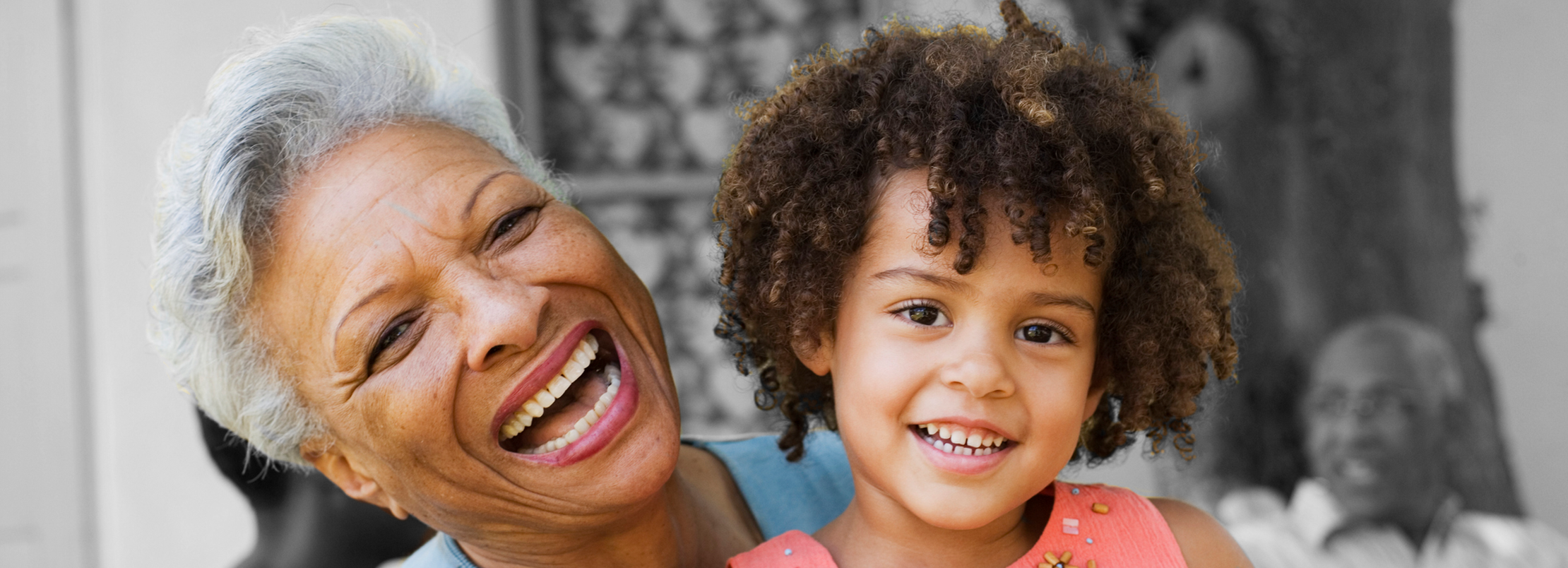 Black grandmother smiling with black grandaughter on her lap