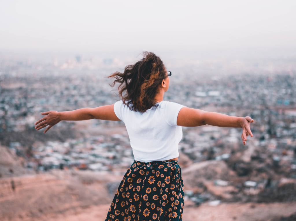 Person standing with arms wide while gazing out at the city below
