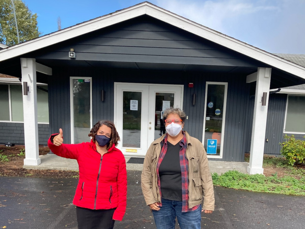 Amara's Scarlett Aldebot-Green, CEO, and Christina Pizaña, Capital Projects and Facilities Manager, high-five in excitement outside Amara's Pierce County office
